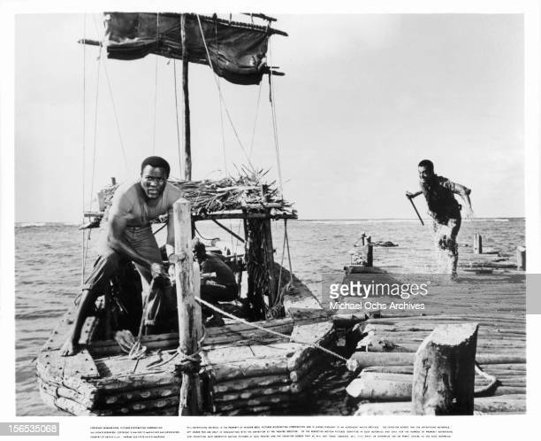 Rafer Johnson unties a docked boat in a scene from the film 'None But The Brave' 1965