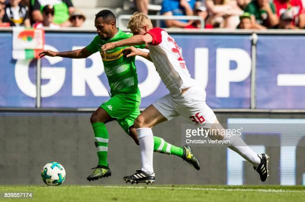Raffael of Borussia Moenchengladbach is chased by Martin Hinteregger of FC Augsburg during a Bundesliga match between FC Augsburg and Borussia...