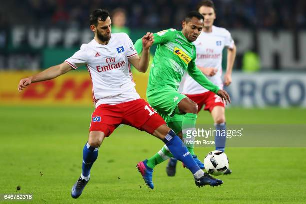 Raffael of Moenchengladbach is challenged by Mergim Mavraj of Hamburg during the DFB Cup quarter final between Hamburger SV and Borussia...