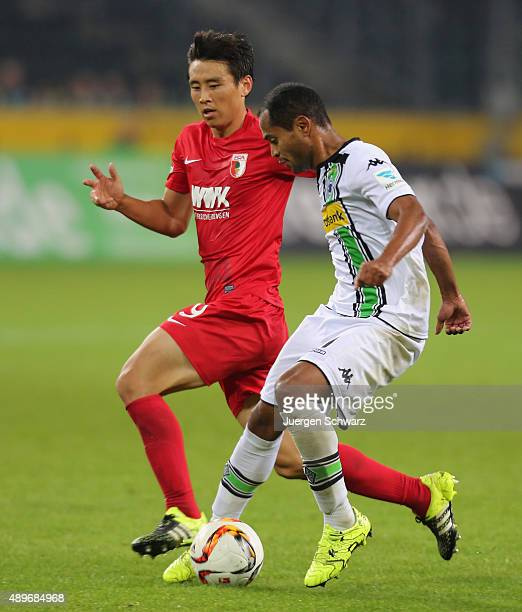 Raffael of Moenchengladbach tackles JaCheol Koo of Augsburg during the Bundesliga match between Borussia Moenchengladbach and FC Augsburg at...