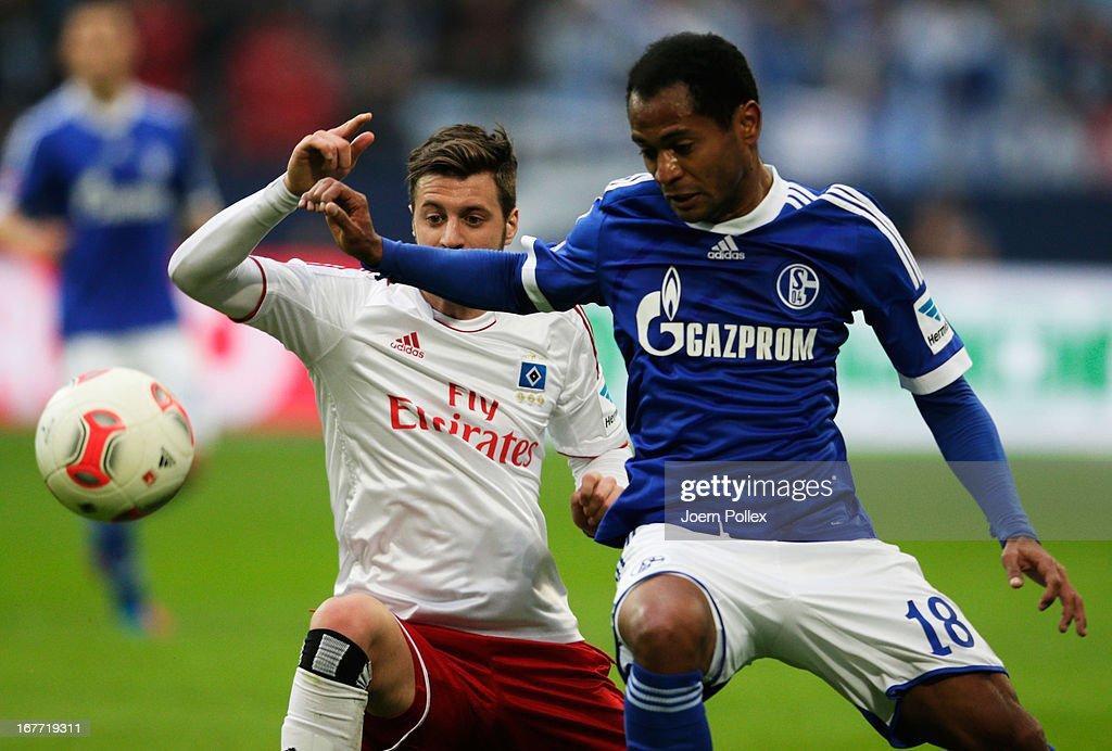 Raffael (R) of Schalke and Jacopo Sala of Hamburg compete for the ball during the Bundesliga match between FC Schalke 04 and Hamburger SV at Veltins-Arena on April 28, 2013 in Gelsenkirchen, Germany.