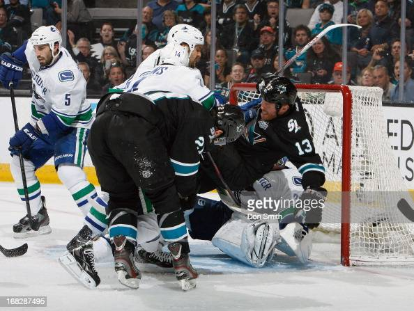 Raffi Torres and TJ Galiardi of the San Jose Sharks try to score against Jason Garrison and Cory Schneider of the Vancouver Canucks in Game Four of...