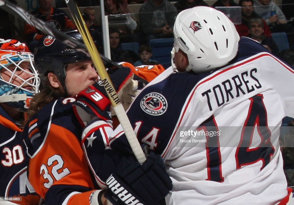 Raffi Torres of the Columbus Blue Jackets and Brendan Witt of the New York Islanders collide at the Nassau Coliseum on December 29 2009 in Uniondale...