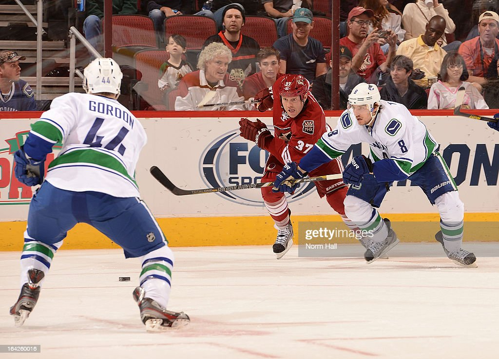 <a gi-track='captionPersonalityLinkClicked' href=/galleries/search?phrase=Raffi+Torres&family=editorial&specificpeople=204612 ng-click='$event.stopPropagation()'>Raffi Torres</a> #37 of the Phoenix Coyotes and <a gi-track='captionPersonalityLinkClicked' href=/galleries/search?phrase=Christopher+Tanev&family=editorial&specificpeople=7228624 ng-click='$event.stopPropagation()'>Christopher Tanev</a> #8 of the Vancouver Canucks race for possession of the puck at Jobing.com Arena on March 21, 2013 in Glendale, Arizona.