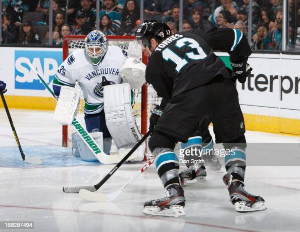 Raffi Torres of the San Jose Sharks handles the puck in front of the net against Cory Schneider of the Vancouver Canucks in Game Four of the Western...