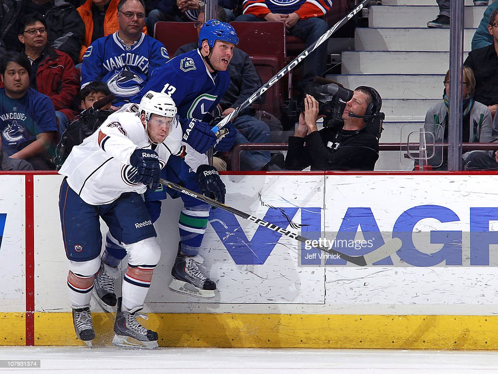 Raffi Torres of the Vancouver Canucks gets checked into the boards by Liam Reddox of the Edmonton Oilers during their game at Rogers Arena on January...