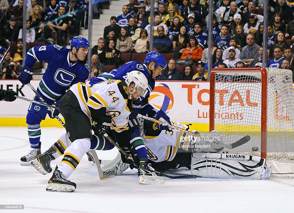 Raffi Torres watches teammate Manny Malhotra of the Vancouver Canucks lift the puck over Tim Thomas of the Boston Bruins for a goal despite being...