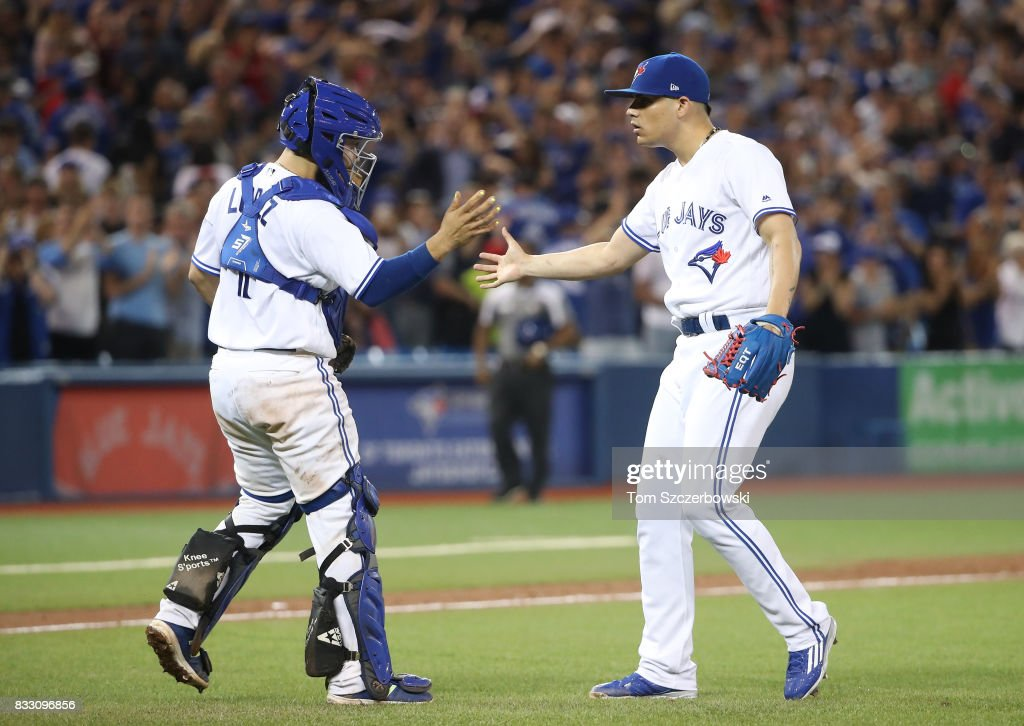 Raffy Lopez #1 of the Toronto Blue Jays celebrates a victory with Roberto Osuna #54 during MLB game action against the Tampa Bay Rays at Rogers Centre on August 16, 2017 in Toronto, Canada.
