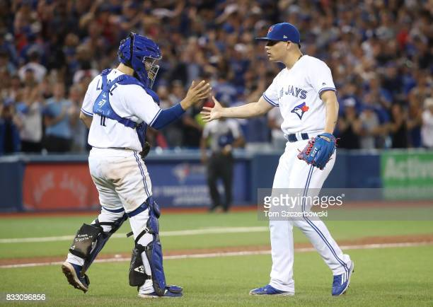 Raffy Lopez of the Toronto Blue Jays celebrates a victory with Roberto Osuna during MLB game action against the Tampa Bay Rays at Rogers Centre on...