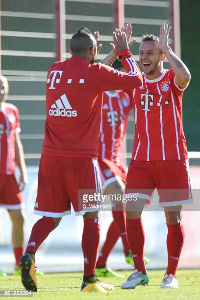 Rafinha and Arturo Vidal of FC Bayern Muenchen joke during a training session at Saebener Strasse training ground on October 15 2017 in Munich Germany