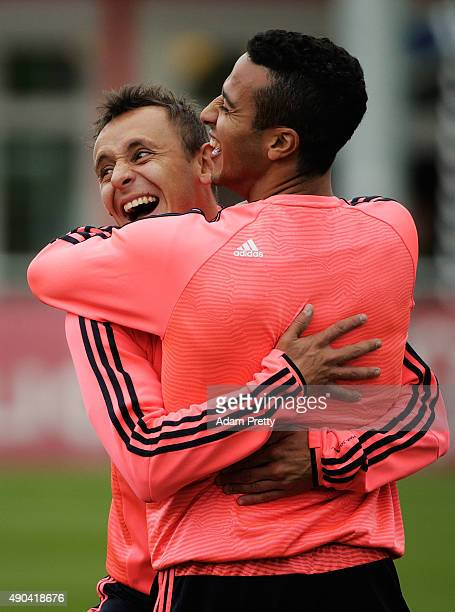 Rafinha and Thiago of Bayern Munich have a cuddle and a laugh while warming up during Bayern Muenchen Training at the Bayern Munich training grounds...