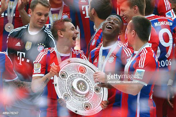 Rafinha his team mate David Alaba and Franck Ribery of Bayern Muenchen celebrate with the Bundesliga championship trophy after the Bundesliga match...