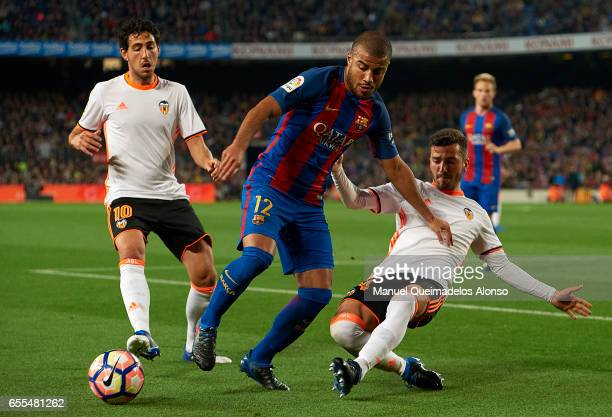 Rafinha of Barcelona is tackled by Jose Luis Gaya of Valencia during the La Liga match between FC Barcelona and Valencia CF at Camp Nou Stadium on...