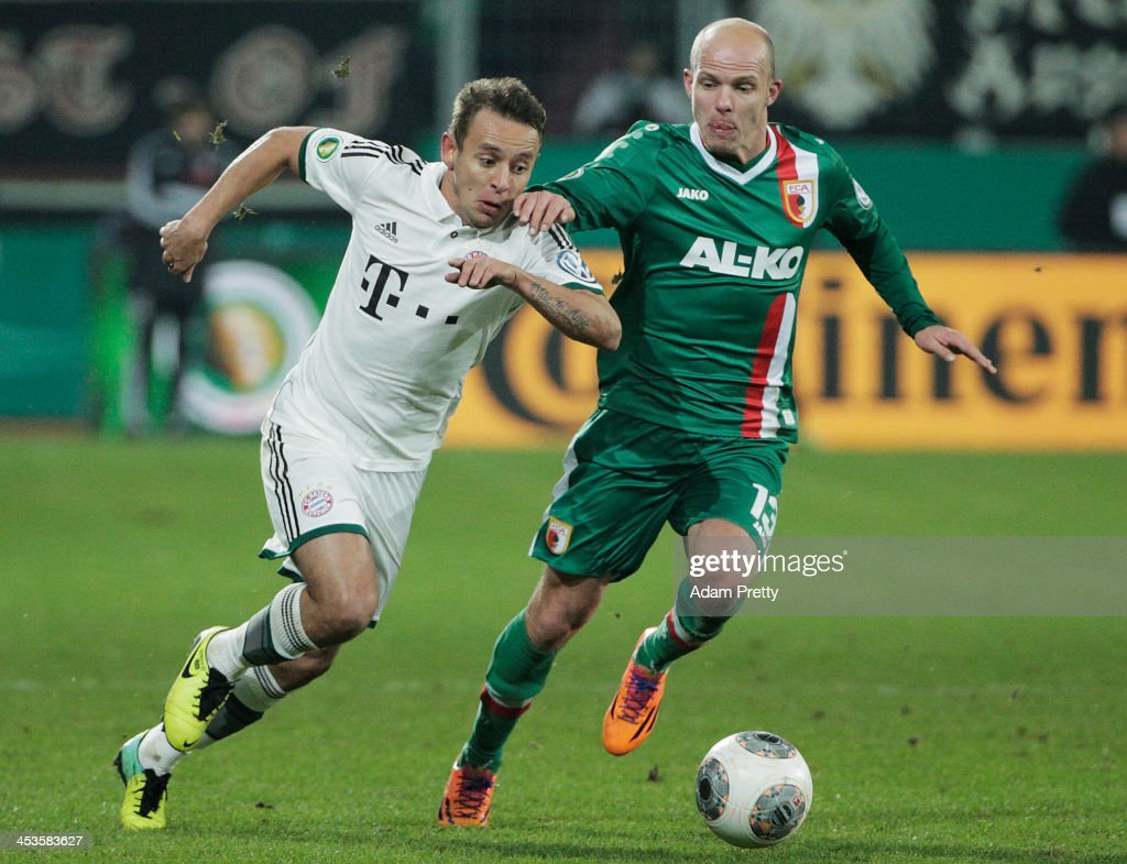 Rafinha of Bayern is challenged by Tobias Werner of Augsburg during the FC Augsburg v Bayern Muenchen DFB Cup match at SGL Arena on December 4, 2013 in Augsburg, Germany.