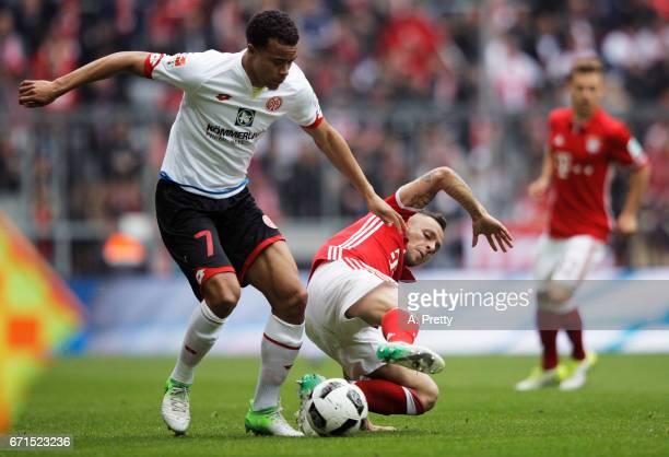 Rafinha of Bayern Munich tackles Robin Quaison of FSV Mainz 05 during the Bundesliga match between Bayern Muenchen and 1 FSV Mainz 05 at Allianz...