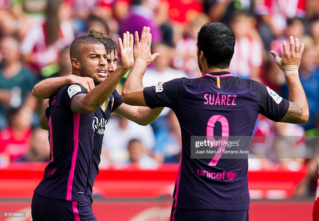 Rafinha of FC Barcelona celebrates with his teammates Luis Suarez of FC Barcelona after scoring his team's second goal during the La Liga match between Real Sporting de Gijon and FC Barcelona at Estadio El Molinon on September 24, 2016 in Gijon, Spain.