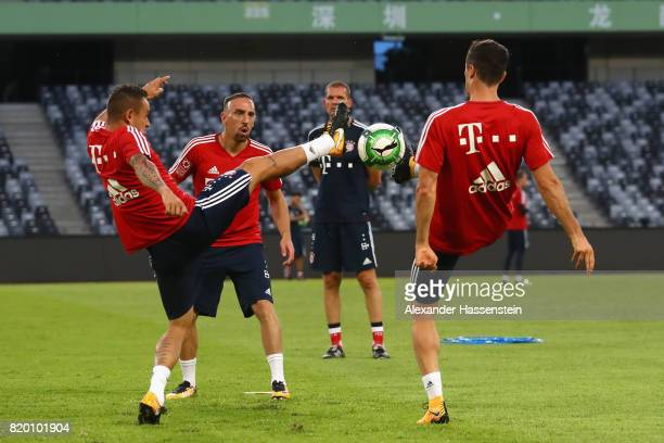 Rafinha of FC Bayern Muenchen battle for the ball with his team mates Franck Ribery and Robert Lewandowski during a training session at Shenzhen...