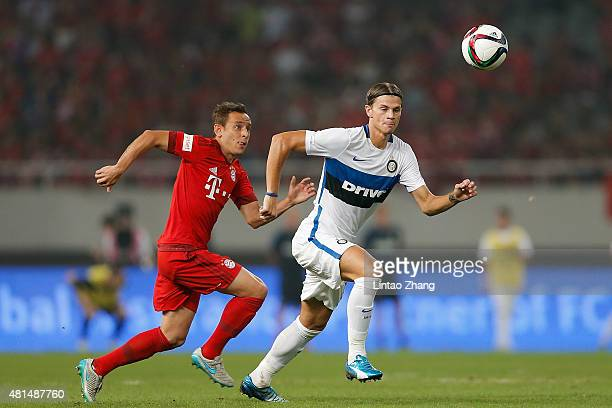 Rafinha of FC Bayern Muenchen challenges Samuele Longo of FC Internazionale during the international friendly match between FC Bayern Muenchen and...