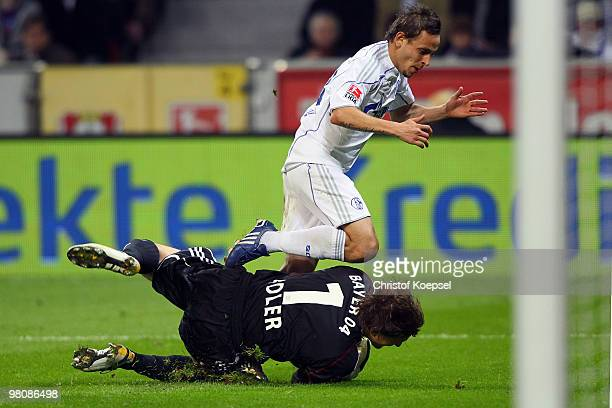 Rafinha of Schalke challenges goalkeeper Rene Adler of Leverkusen during the Bundesliga match between Bayer Leverkusen and FC Schalke 04 at the...