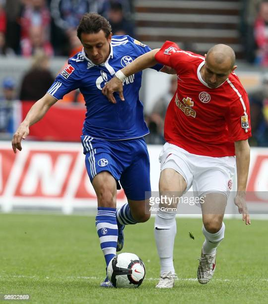 Rafinha of Schalke is challenged by Elkin Soto of Mainz during the Bundesliga match between FSV Mainz 05 and FC Schalke 04 at the Bruchweg Stadium on...