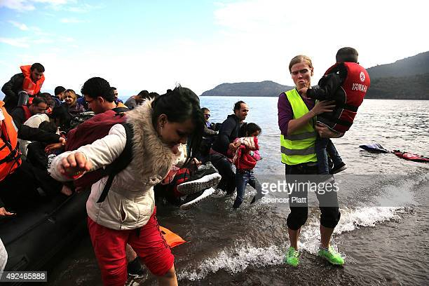 A raft carrying Syrian and Iraqi refugees arrives on the island of Lesbos from Turkey on October 13 2015 in Mitilini Greece Dozens of rafts are still...