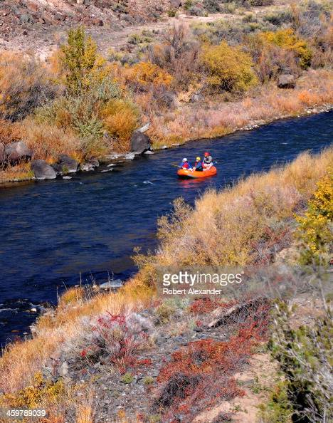 Rafters float along a smooth stretch of the Rio Grande River near Taos New Mexico The stretch of river and the gorge it carved into the desert...