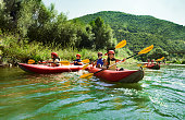 Several two people team inflatable canoes rafting in a calm waters with beautiful surrounding.