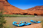 Three empty rafts on the shore of Colorado River near Moab in Utah against a beautiful backdrop of red rocks along the scenic byway 128.