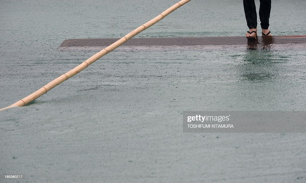 A raftsman, a member of the Kiba 'Kakunori' preservation society, performs a stunt on a floating square lumber at a local festival in Tokyo on October 20, 2013. The stunt is derived by managing to ride on a floating square lumber during the daily work of lumberjacks during the Edo period (1603-1868).