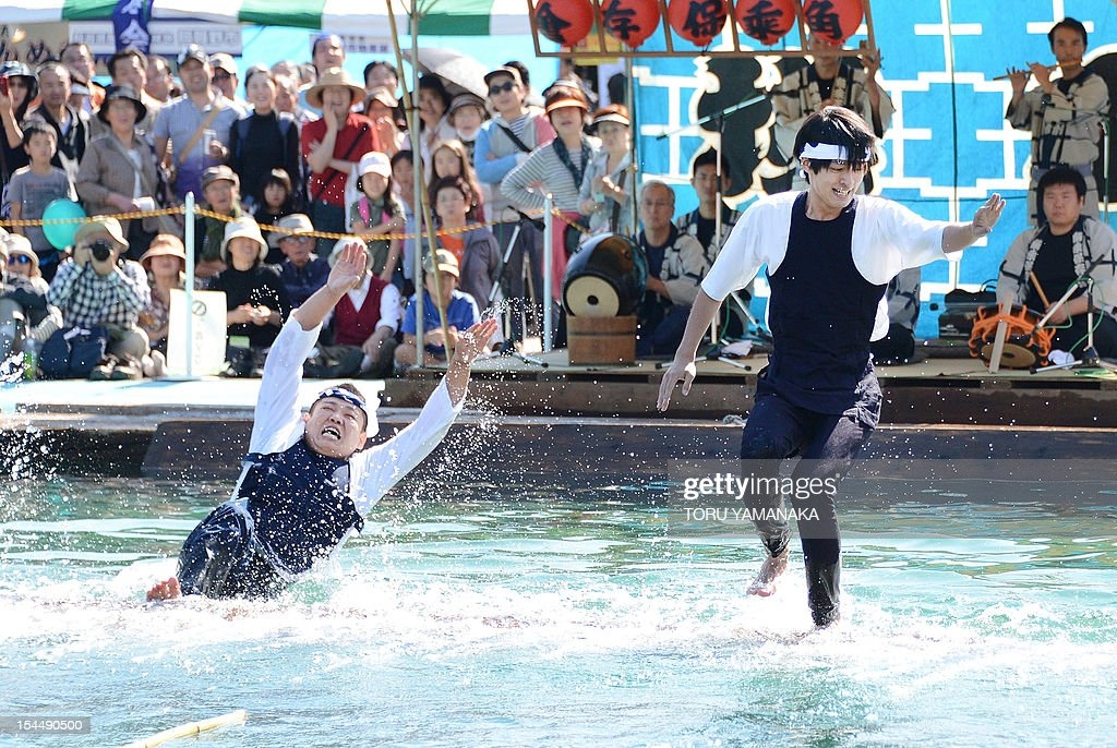 A raftsman (L), member of the Kiba 'kakunori' preservation society, falls down into the water from a floating square timber during his stunt with another member at a local festival in Tokyo on October 21, 2012. The stunt derived from lumberjacks' daily work in the Edo period (1603-1868), when they made rafts with fire-hooks in their hands standing on floating lumbers. AFP PHOTO/Toru YAMANAKA