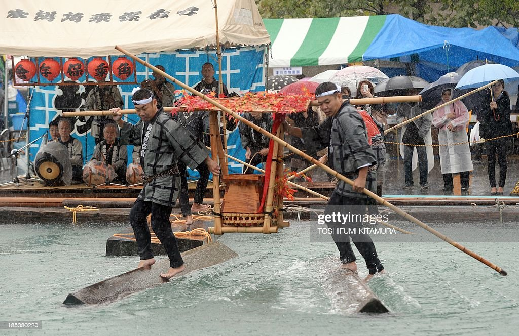 Raftsmen, members of the Kiba 'Kakunori' preservation society, perform a stunt on a floating square lumber at a local festival in Tokyo on October 20, 2013. The stunt is derived by managing to ride on a floating square lumber during the daily work of lumberjacks during the Edo period (1603-1868).