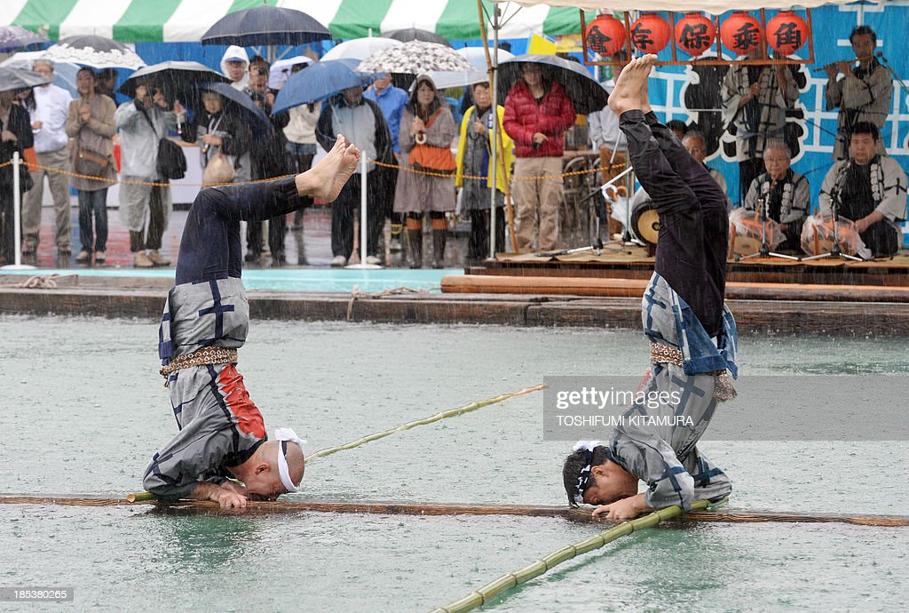 Raftsmen, members of the Kiba 'kakunori' preservation society, perform a stunt on a floating square lumbers at a local festival in Tokyo on October 20, 2013. The stunt is derived by managing to ride on a floating square lumber during the daily work of lumberjacks during the Edo period (1603-1868). AFP PHOTO / TOSHIFUMI KITAMURA