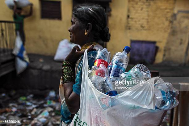 A rag picker carries a bag of collected plastic bottles in the Govandi area of Mumbai India on Wednesday March 11 2015 Mumbai is running out of space...