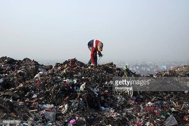A rag picker sorts through garbage picking out recyclable materials to sell at the Ghazipur landfill site in the east of New Delhi India on Friday...