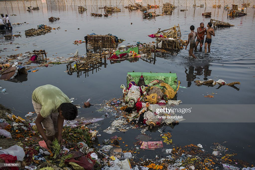 A rag picker sorts through refuse left over from Hindu devotees immersing an idols of Goddess Durga into the Yamuna river on the last day of the Durga Puja festival on October 24, 2012 in Delhi, India. The festival celebrates the worship of the Hindu Goddess Durga, who in Hindu Mythology is celebrated as the Goddess of power and the victor of good over evil.