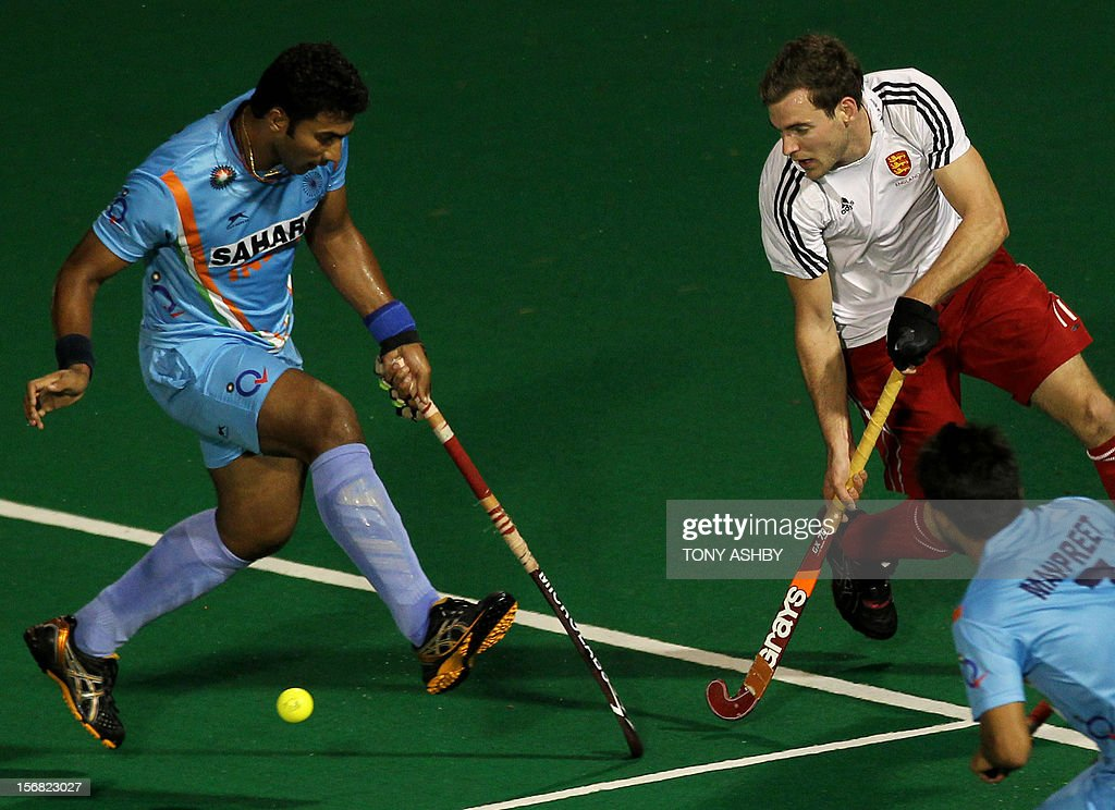 Raghuntha Vokkaliga Ramachandra of India (L) challenges Ally Brogdon of England (R) during their men's match at the International Super Series hockey tournament in Perth on November 22, 2012.