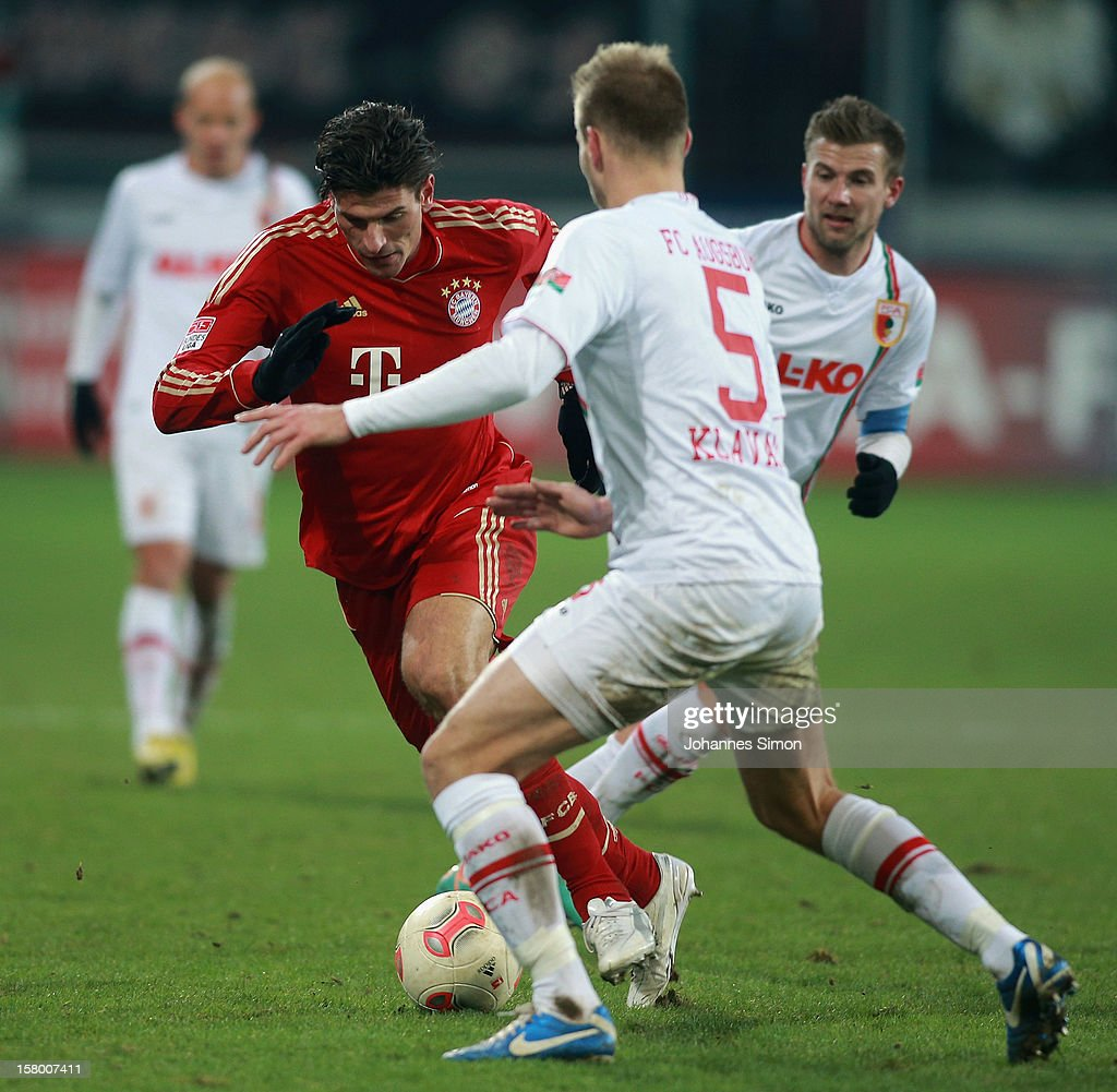 Ragnar Klavan (C) and <a gi-track='captionPersonalityLinkClicked' href=/galleries/search?phrase=Daniel+Baier&family=editorial&specificpeople=706624 ng-click='$event.stopPropagation()'>Daniel Baier</a> (R) of Augsburg fight for the ball with <a gi-track='captionPersonalityLinkClicked' href=/galleries/search?phrase=Mario+Gomez+-+Soccer+Player&family=editorial&specificpeople=635161 ng-click='$event.stopPropagation()'>Mario Gomez</a> (L) of Bayern during the Bundesliga match between FC Augsburg and FC Bayern Muenchen at SGL Arena on December 8, 2012 in Augsburg, Germany.