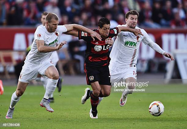 Ragnar Klavan and Daniel Baier of FC Augsburg challenge Chicharito of Bayer Leverkusen during the Bundesliga match between Bayer Leverkusen and FC...