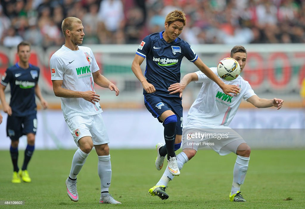 Ragnar Klavan (L) and Dominik Kohr (R) of FC Augsburg challenge Genki Haraguchi (C) of Hertha BSC during the Bundesliga match between FC Augsburg and Hertha BSC at WWK-Arena on August 15, 2015 in Augsburg, Germany.