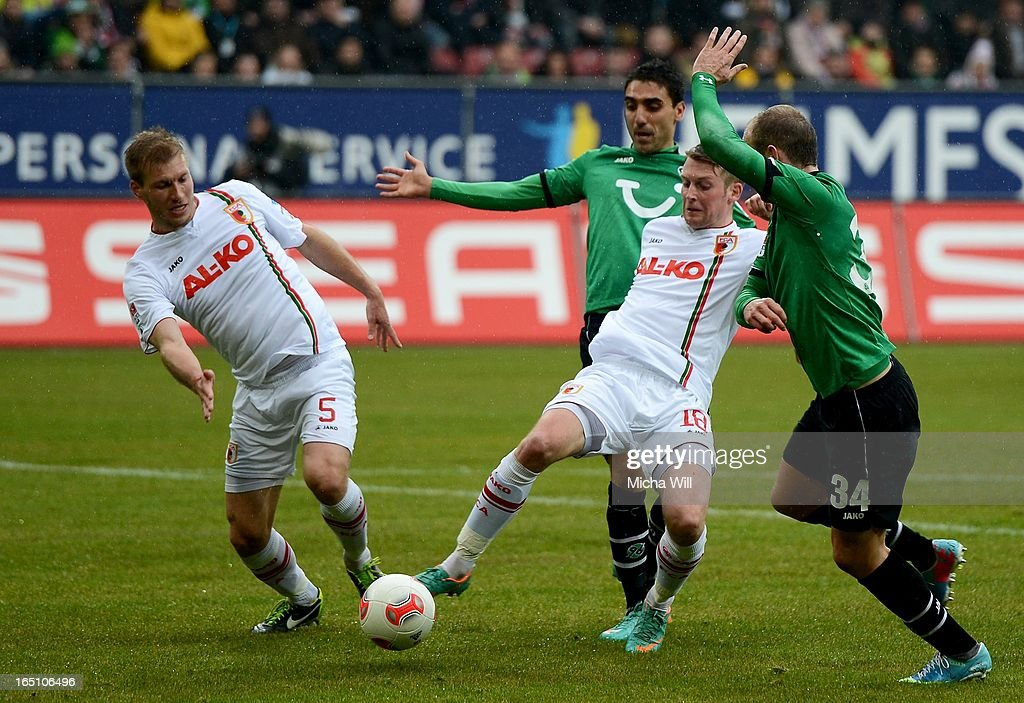 Ragnar Klavan (L) and <a gi-track='captionPersonalityLinkClicked' href=/galleries/search?phrase=Jan-Ingwer+Callsen-Bracker&family=editorial&specificpeople=758385 ng-click='$event.stopPropagation()'>Jan-Ingwer Callsen-Bracker</a> (2nd R) of Augsburg are fighting with Mohammed Abdellaoue (2nd L) and <a gi-track='captionPersonalityLinkClicked' href=/galleries/search?phrase=Konstantin+Rausch&family=editorial&specificpeople=2146604 ng-click='$event.stopPropagation()'>Konstantin Rausch</a> of Hannover for the Ball during the Bundesliga match between FC Augsburg and Hannover 96 at SGL Arena on March 30, 2013 in Augsburg, Germany.