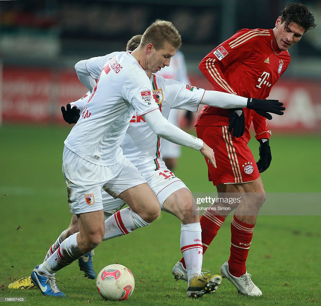 Ragnar Klavan and Marcel de Jong of Augsburg fight for the ball with <a gi-track='captionPersonalityLinkClicked' href=/galleries/search?phrase=Mario+Gomez+-+Soccer+Player&family=editorial&specificpeople=635161 ng-click='$event.stopPropagation()'>Mario Gomez</a> of Bayern during the Bundesliga match between FC Augsburg and FC Bayern Muenchen at SGL Arena on December 8, 2012 in Augsburg, Germany.