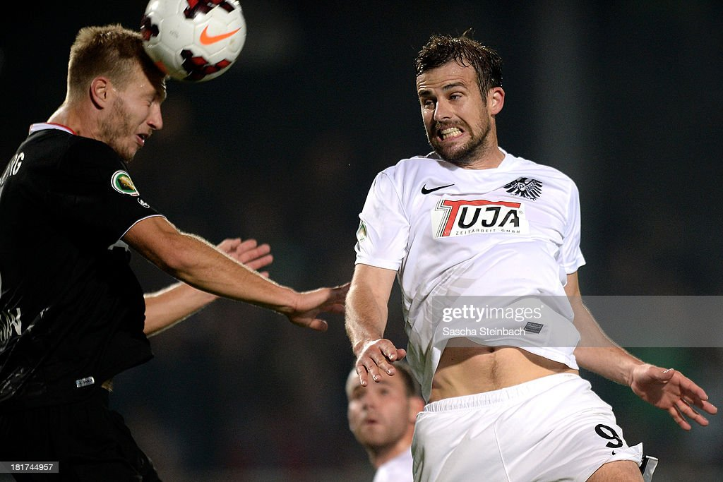 Ragnar Klavan of Augsburg and Matthew Taylor of Muenster jump for a header during DFB Cup second round match between Preussen Muenster and FC Augsburg at Preussenstadion on September 24, 2013 in Muenster, Germany.