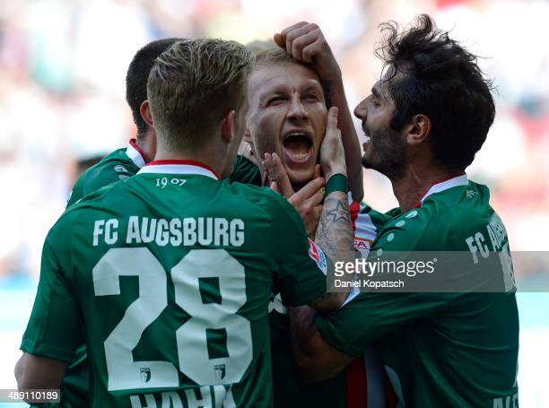 Ragnar Klavan of Augsburg celebrates his team's first goal with team mates Andre Hahn and Halil Altintop during the Bundesliga match between FC...