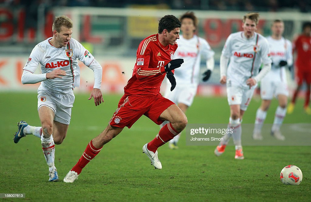 Ragnar Klavan (L) of Augsburg fights for the ball with <a gi-track='captionPersonalityLinkClicked' href=/galleries/search?phrase=Mario+Gomez+-+Soccer+Player&family=editorial&specificpeople=635161 ng-click='$event.stopPropagation()'>Mario Gomez</a> (2L) of Bayern during the Bundesliga match between FC Augsburg and FC Bayern Muenchen at SGL Arena on December 8, 2012 in Augsburg, Germany.