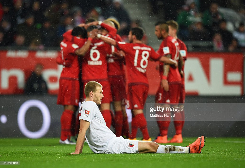 Ragnar Klavan of Augsburg looks dejected as Robert Lewandowski of Bayern Munich celebrates with team mates as he scores their first goal during the Bundesliga match between FC Augsburg and FC Bayern Muenchen at SGL Arena on February 14, 2016 in Augsburg, Germany.
