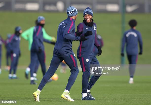 Raheem Sterling and Fabian Delph joke during training at Manchester City Football Academy on December 12 2017 in Manchester England