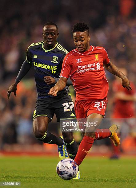 Raheem Sterling of Liverpool and Albert Adomah of Middlesbrough compete during the Capital One Cup Third Round match between Liverpool and...