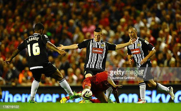 Raheem Sterling of Liverpool battles with Joss Labadie and Mark Fotheringham of Notts County during the Capital One Cup Second Round between...