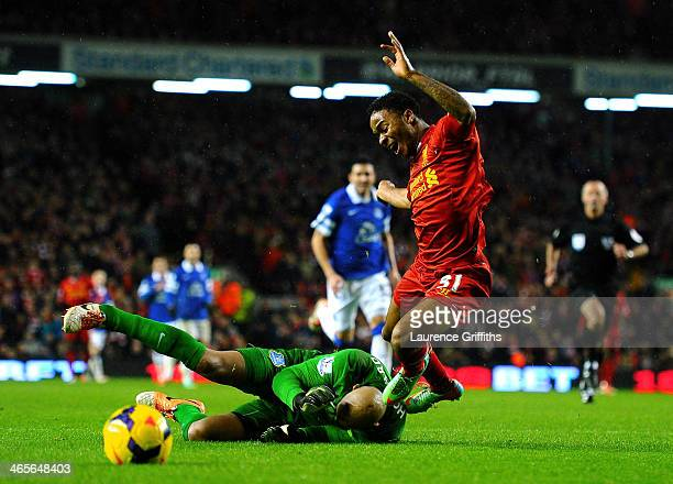 Raheem Sterling of Liverpool is brought down for a penalty by goalkeeper Tim Howard of Everton during the Barclays Premier League match between...