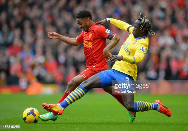 Raheem Sterling of Liverpool is challenged by Bacary Sagna of Arsenal during the Barclays Premier League match between Liverpool and Arsenal at...